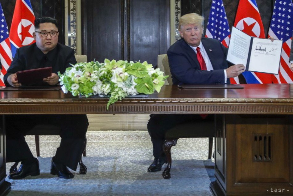 Americký prezident Donald Trump (vpravo) a severokórejský líder Kim Čong-un pózujú po podpise komplexnej dohody, ktorej obsah nebol zverejnený počas historického stretnutia v Singapure 12. júna 2018. Foto: TASR/AP