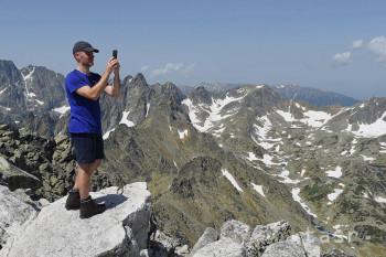 Na snímke turista fotografuje pohľady na okolité štíty na vrchole Slavkovského štítu (2 452 metrov nad morom) vo Vysokých Tatrách.