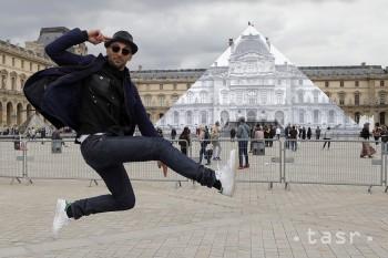 Na snímke francúzsky pouličný umelec JR pózuje pred sklenenou pyramídou Múzea Louvre, ktorá je pokrytá veľkým obrazom ako súčasť jeho projektu 23. mája 2016 v Paríži. Odvážna inštalácia od umelca JR je vytvorená tak, aby pyramída Múzea Louvre pôsobila, že ako keby tam nebola.
